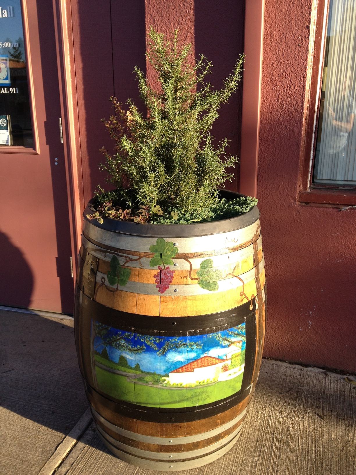 Wine barrel with plants and painted with landscape scene